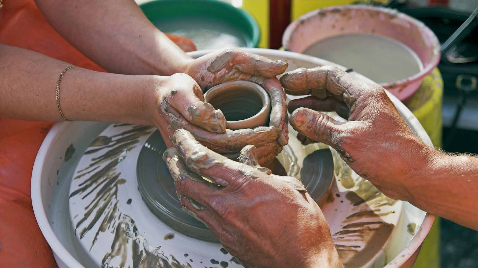 a couple on a date making clay pottery