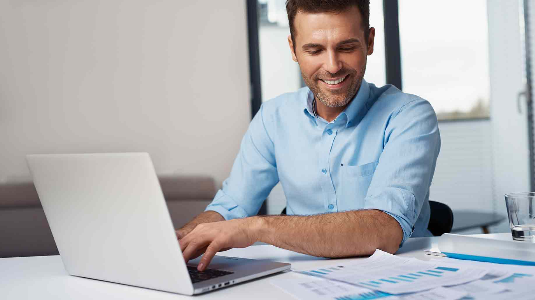 smiling man entering data to laptop at home