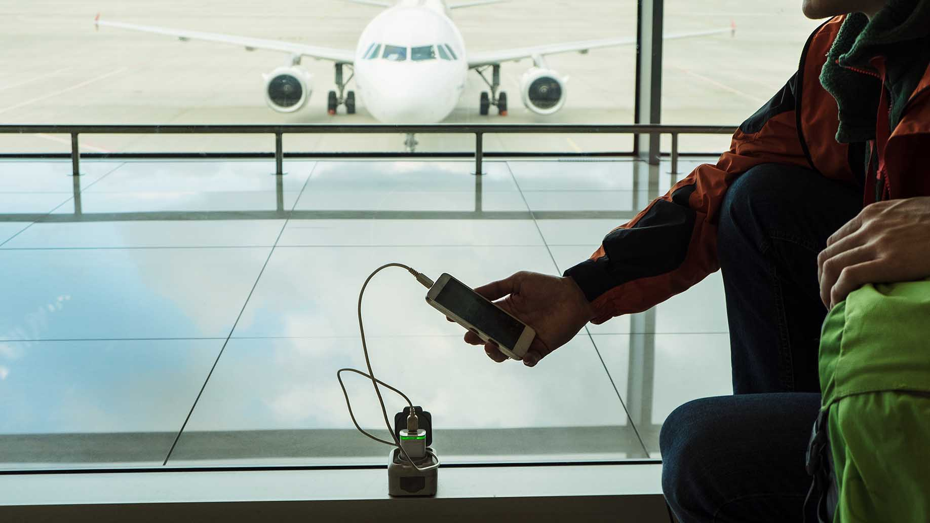 passenger charging mobile device at the lounge of airport terminal