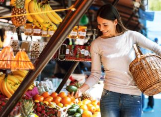 young female buys fruits on steet market
