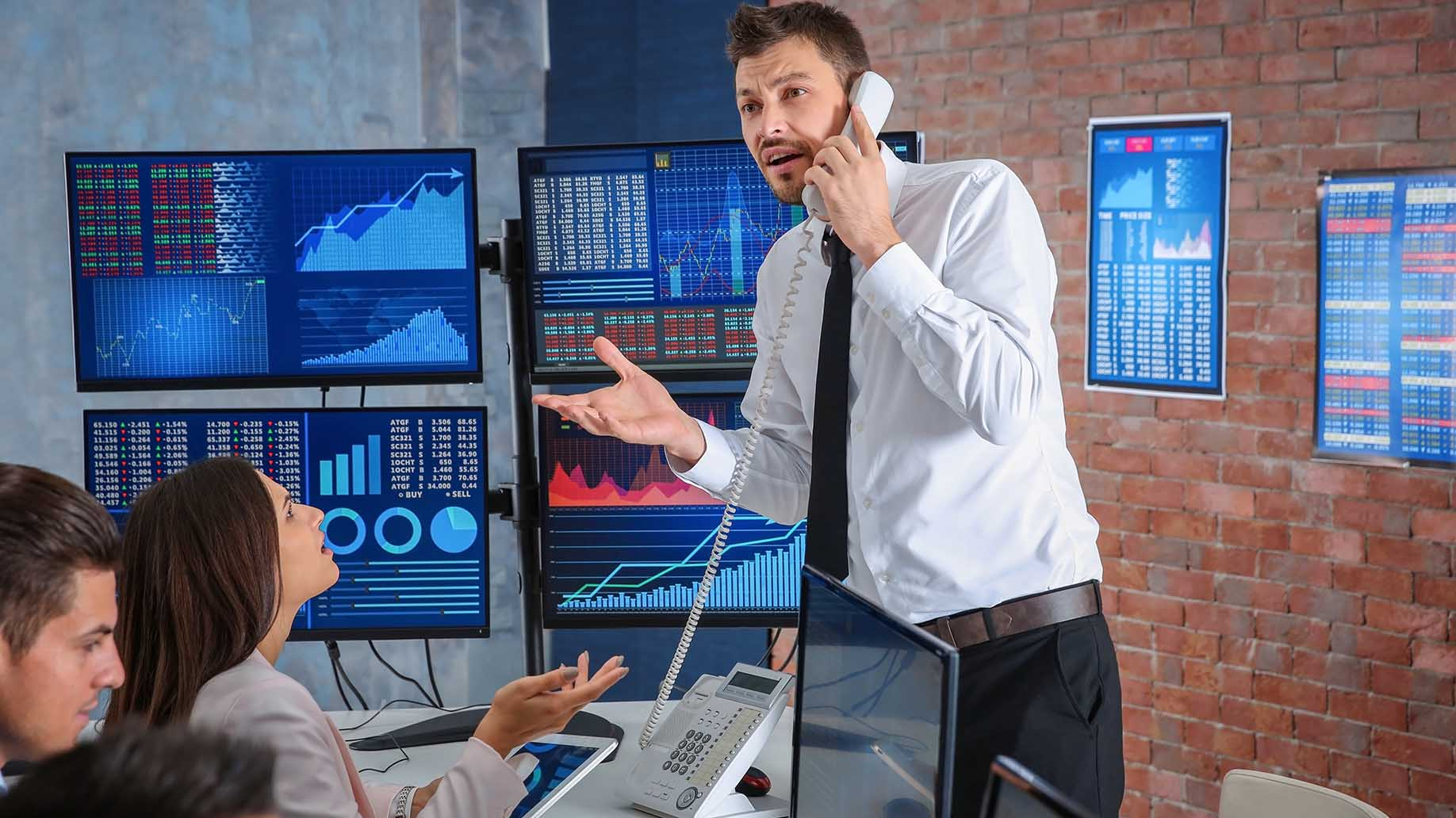 stock trader standing talking to phone
