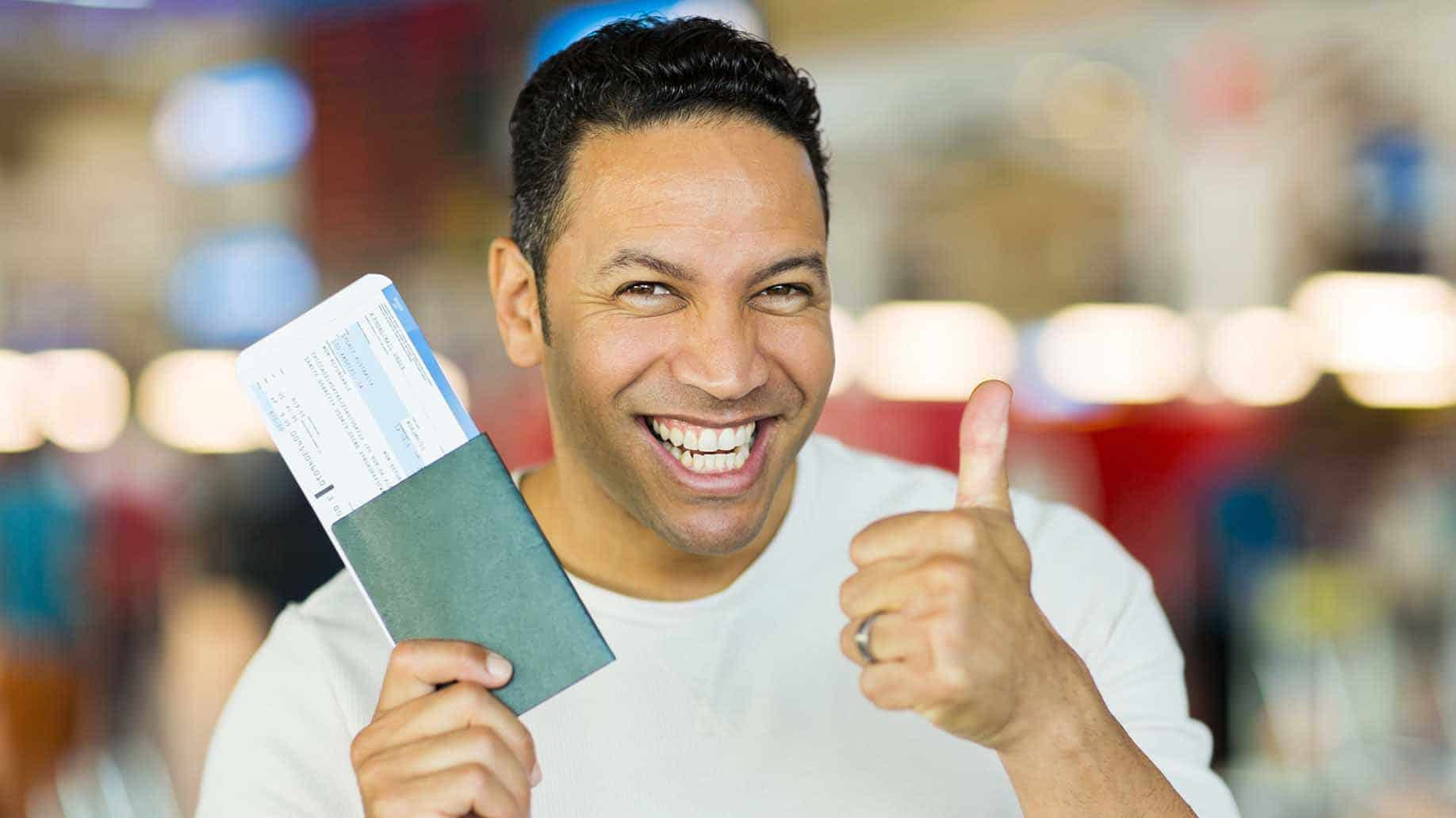 happy man giving thumbs up at airport while holding boarding pass