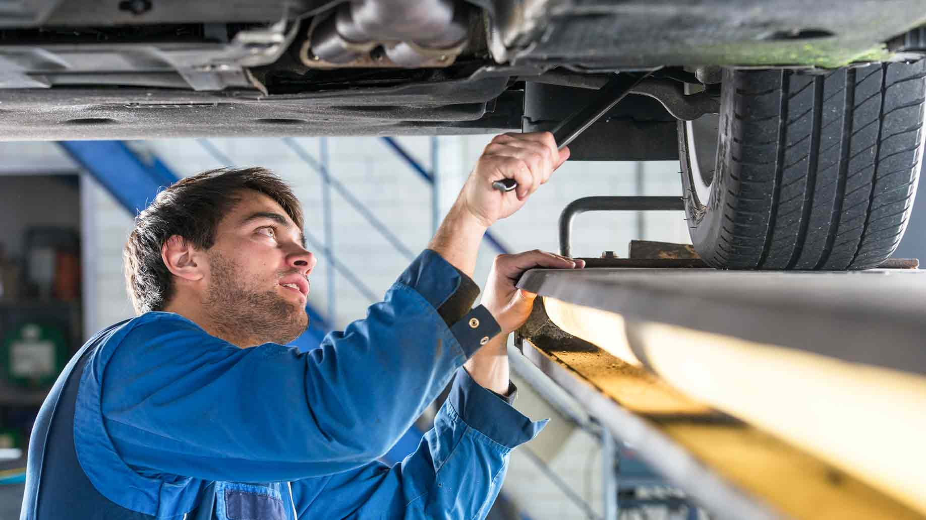 mechanic examining suspension vehicle steel rod