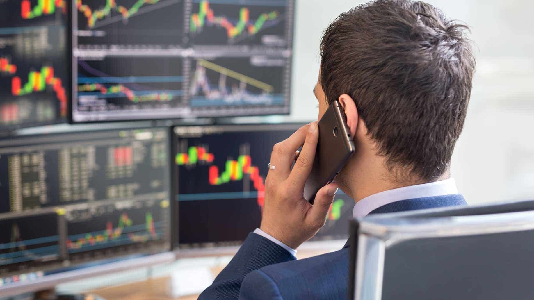 man talking on phone while analyzing stocks