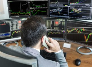 stock broker analyzing charts and data on multiple computer screens