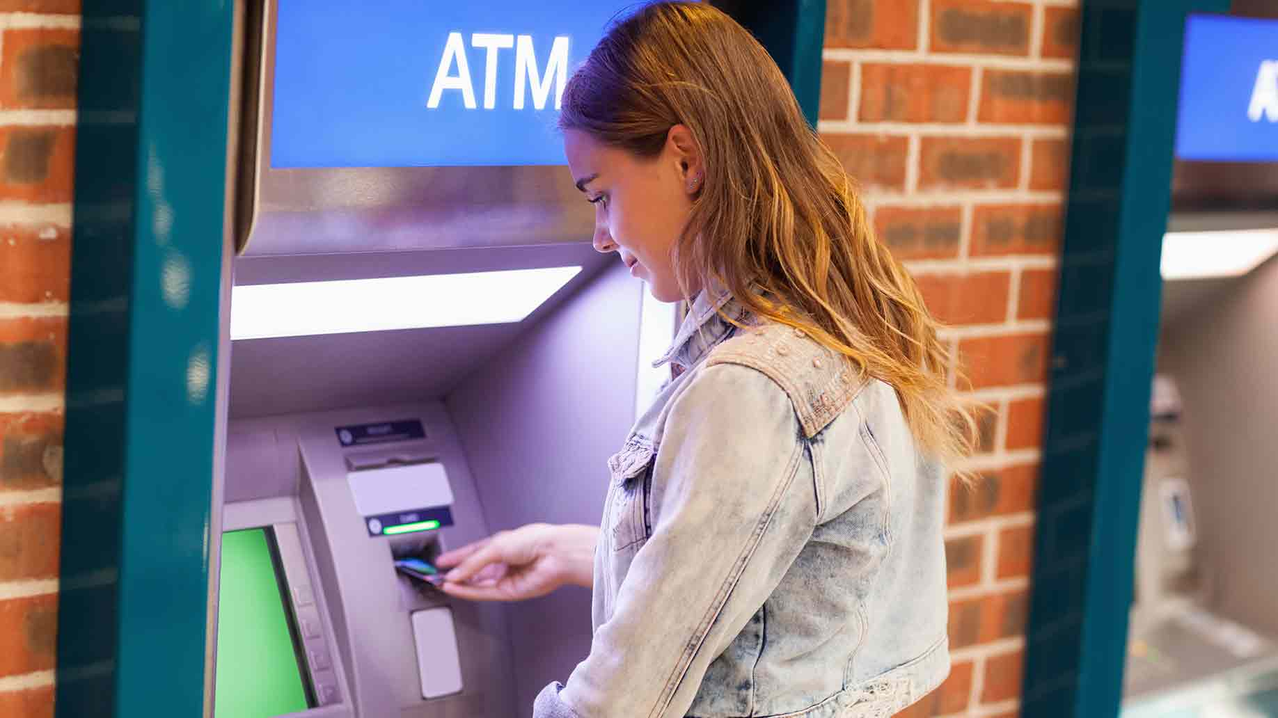 brunette student withdrawing cash at atm machine