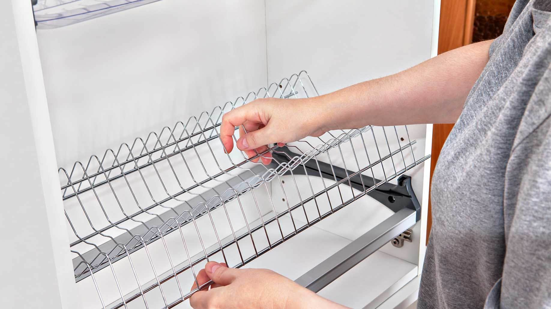 woman placing a wire shelf inside a cabinet