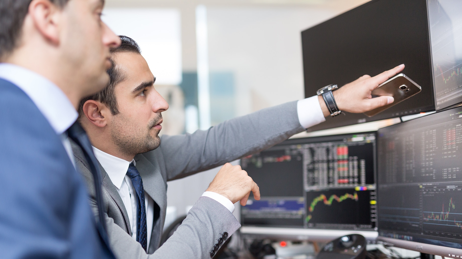 stock brokers looking at the graph in multiple computer screens