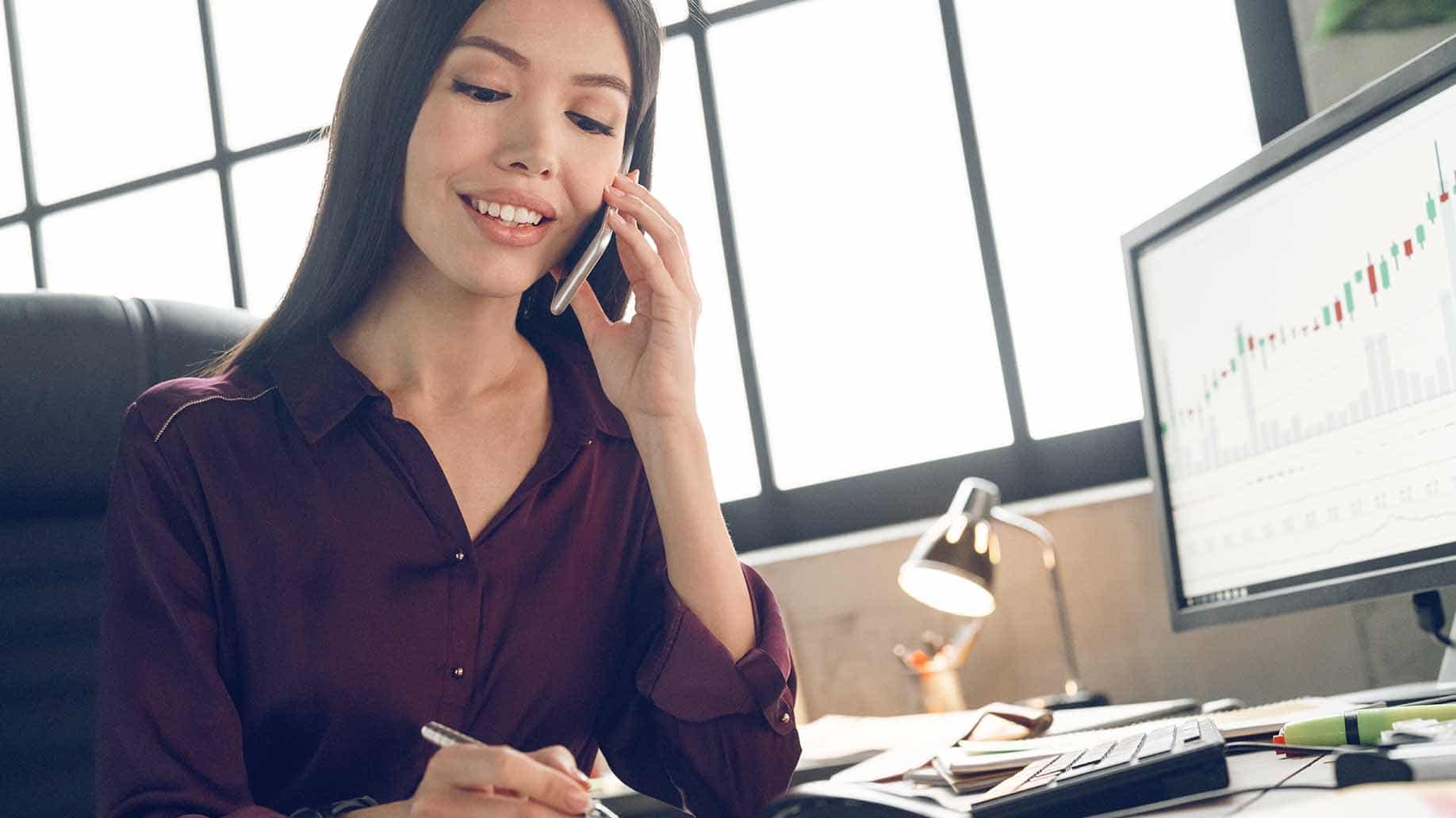 businesswoamn smiling talking to phone beside computer desktop