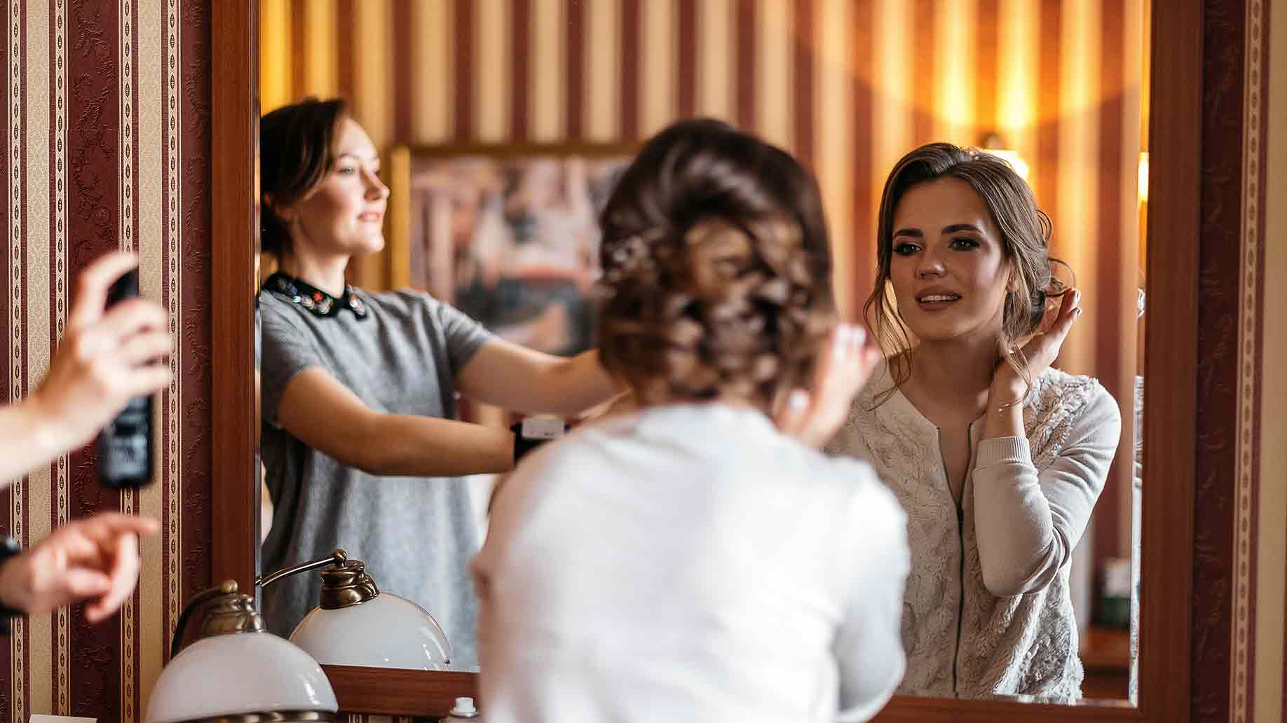 happy bride admires her reflection in the mirror doing her hairstyle