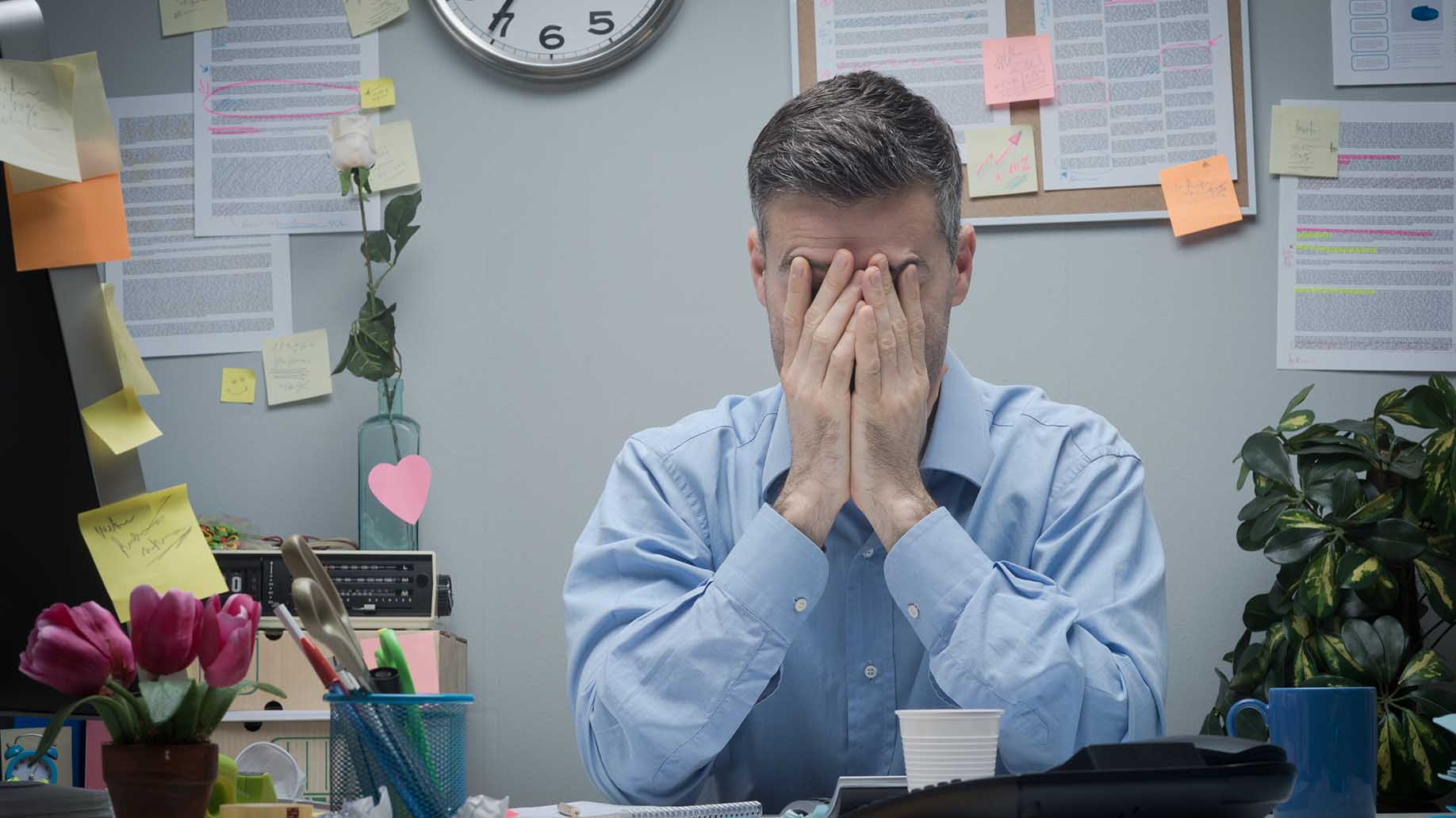 exhausted office worker with hands in head problematic
