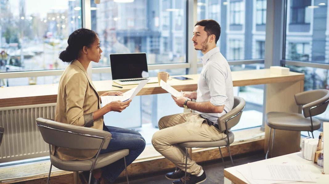 professional human resources manager conducting interview with confident male candidate
