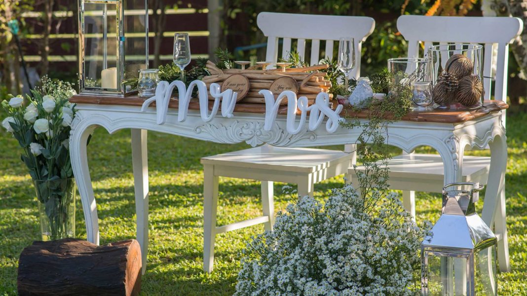wedding on seaside withe table and chairs beside flowers