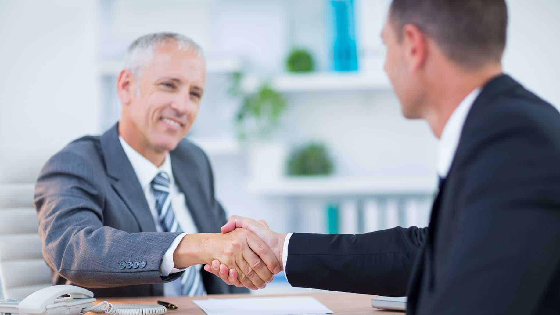 two businessmen shaking hands in the office