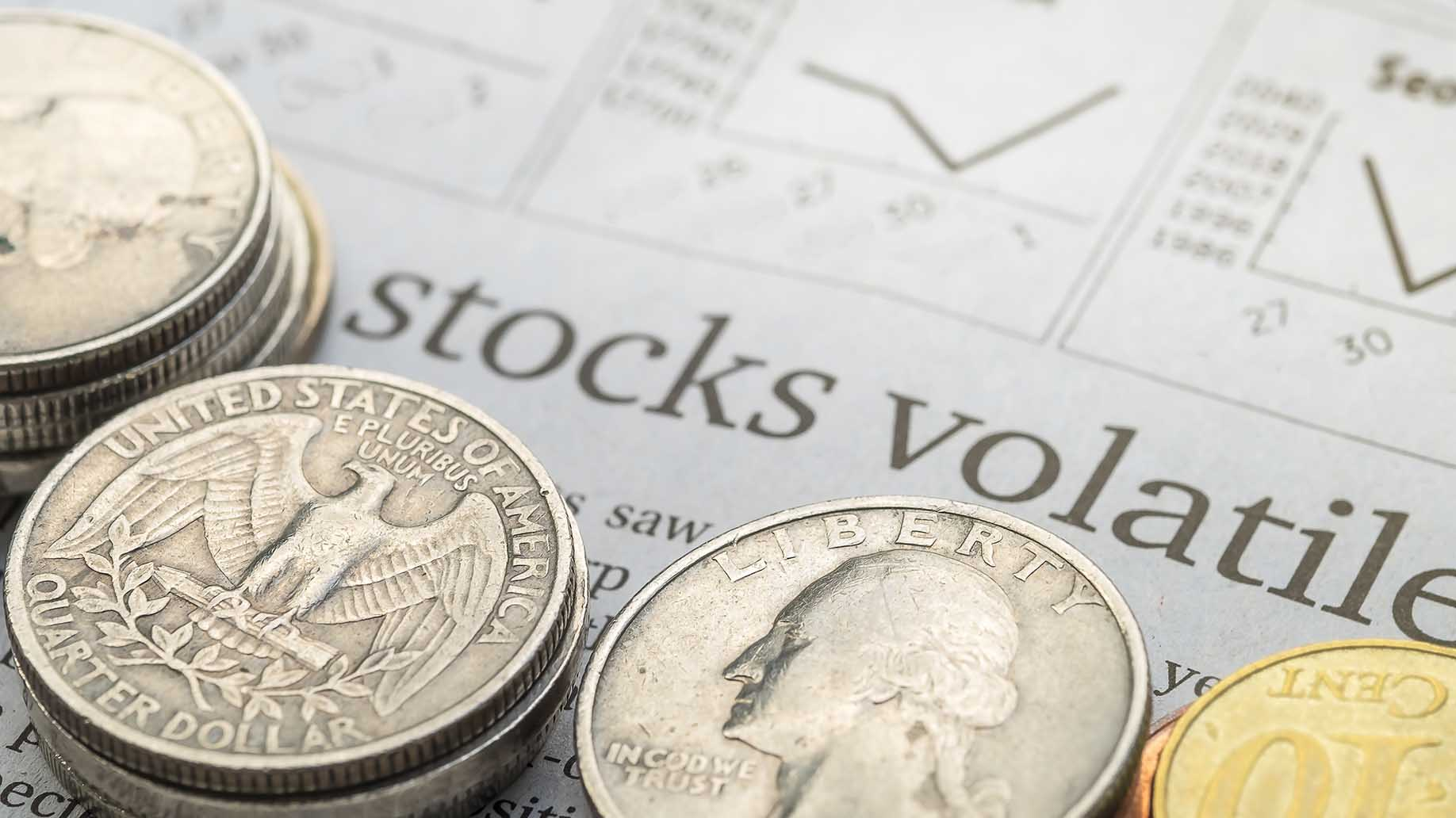 stock market page showing stock volatile word in newpaper with coins