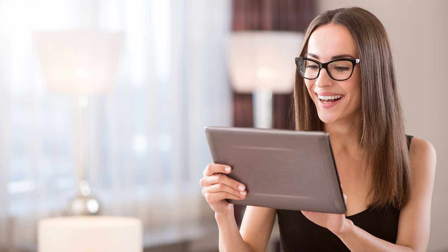 woman smiling holding tablet
