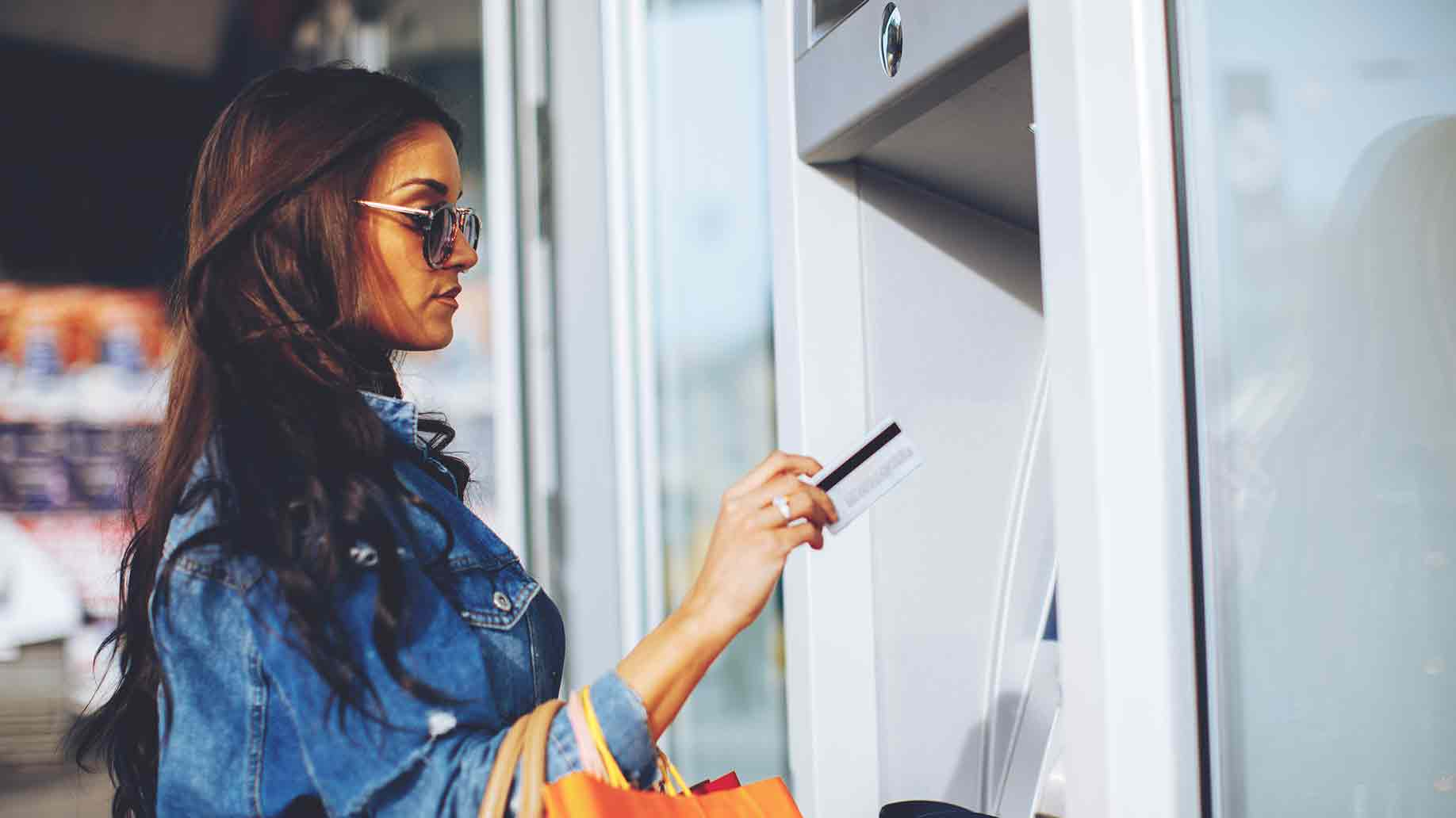 woman withdrawing money from credit card at atm machine