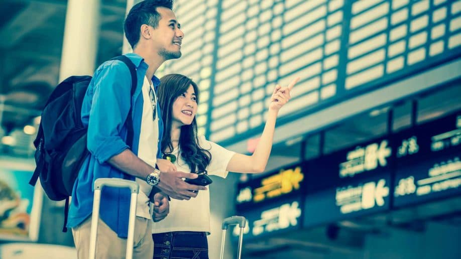 asian couple traveler holding smart mobile?