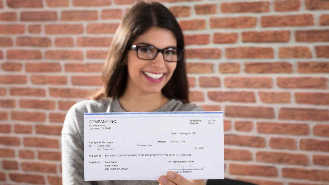 closeup smiling woman showing company cheque?