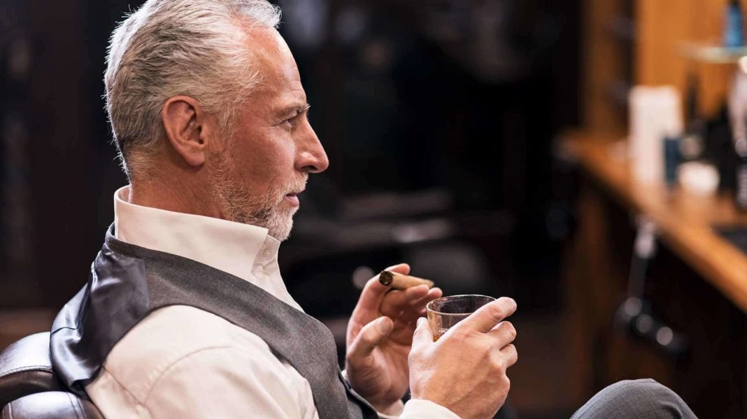 man sitting while holding glass and cigar