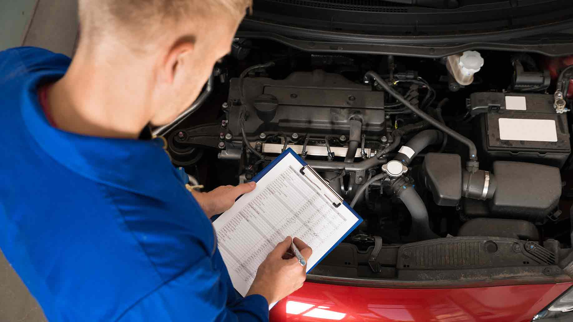 mechanic standing near car writing on clipboard in garage