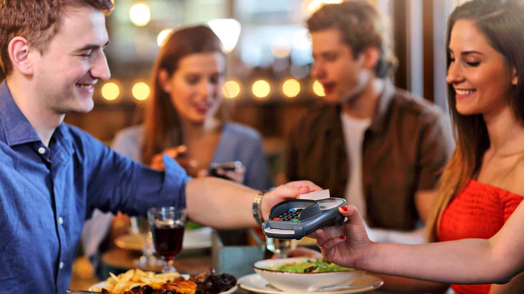 group of fFriends paying for meal in restaurant
