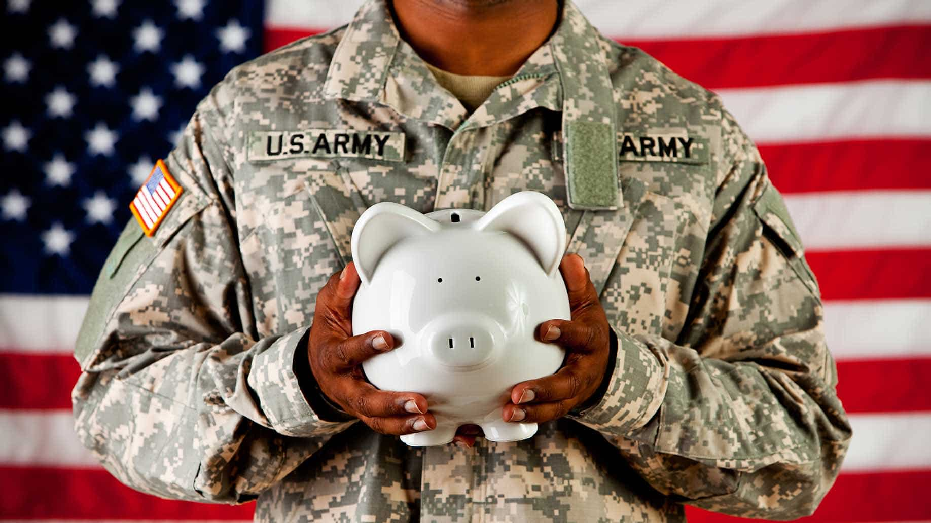soldier holding piggy bank