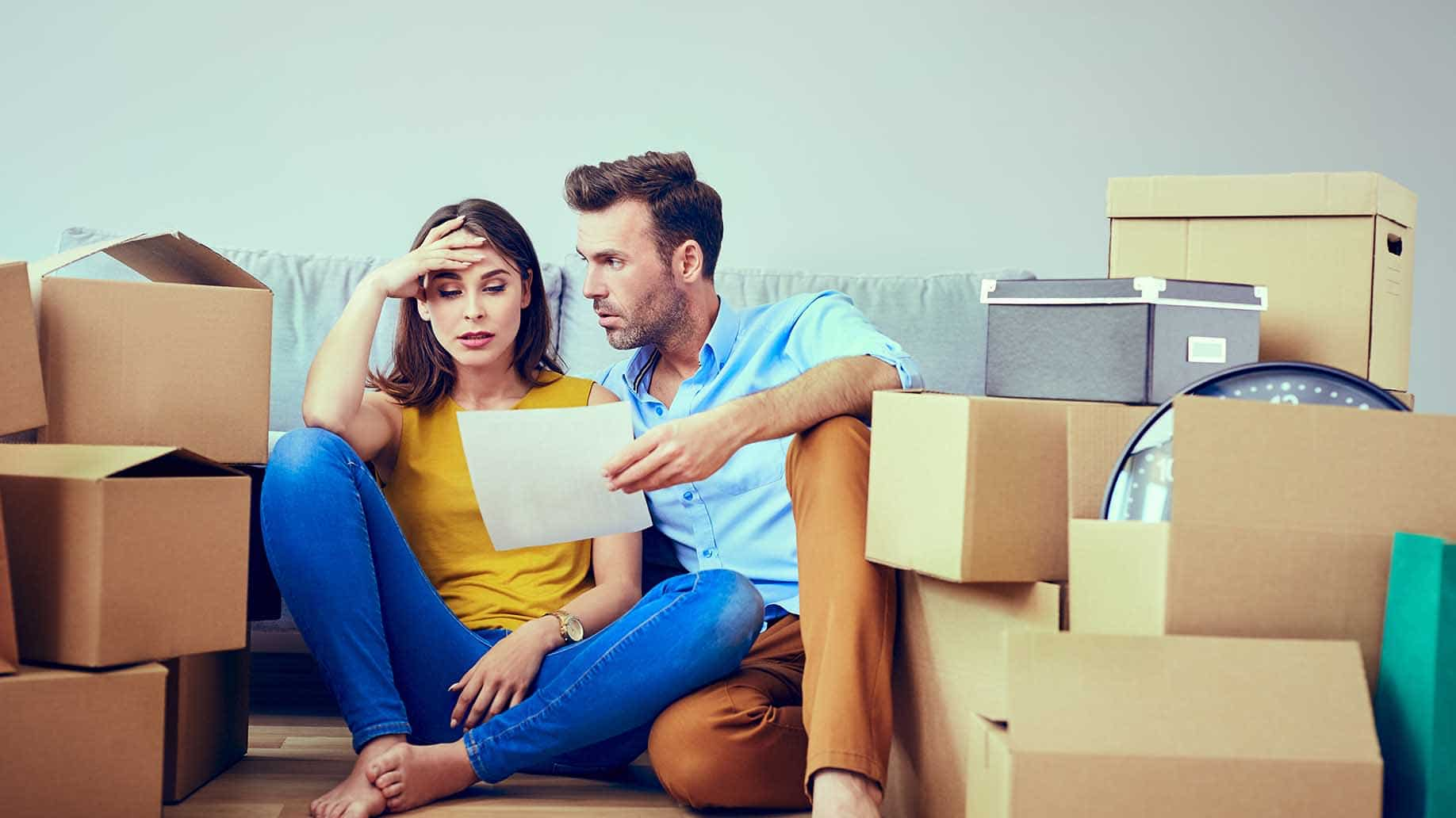 worried couple reading agreement after moving