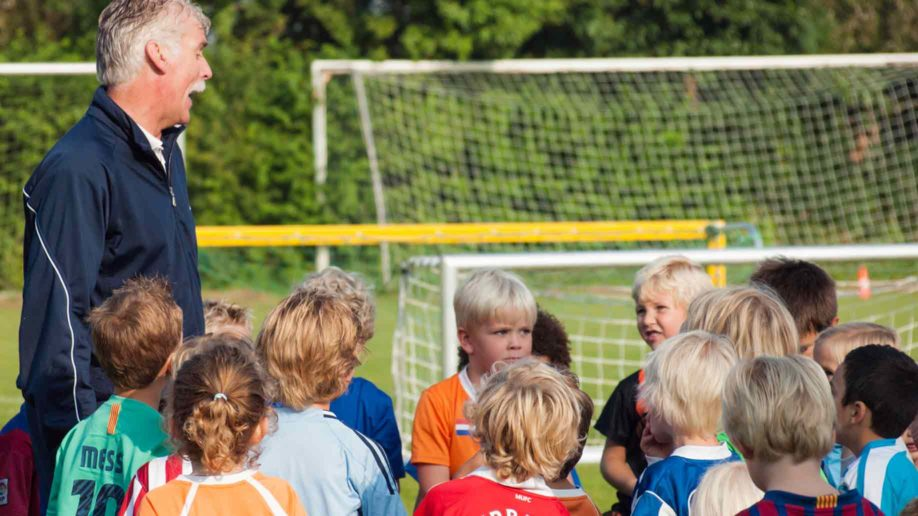 kids listening instruction from a coach during soccer training