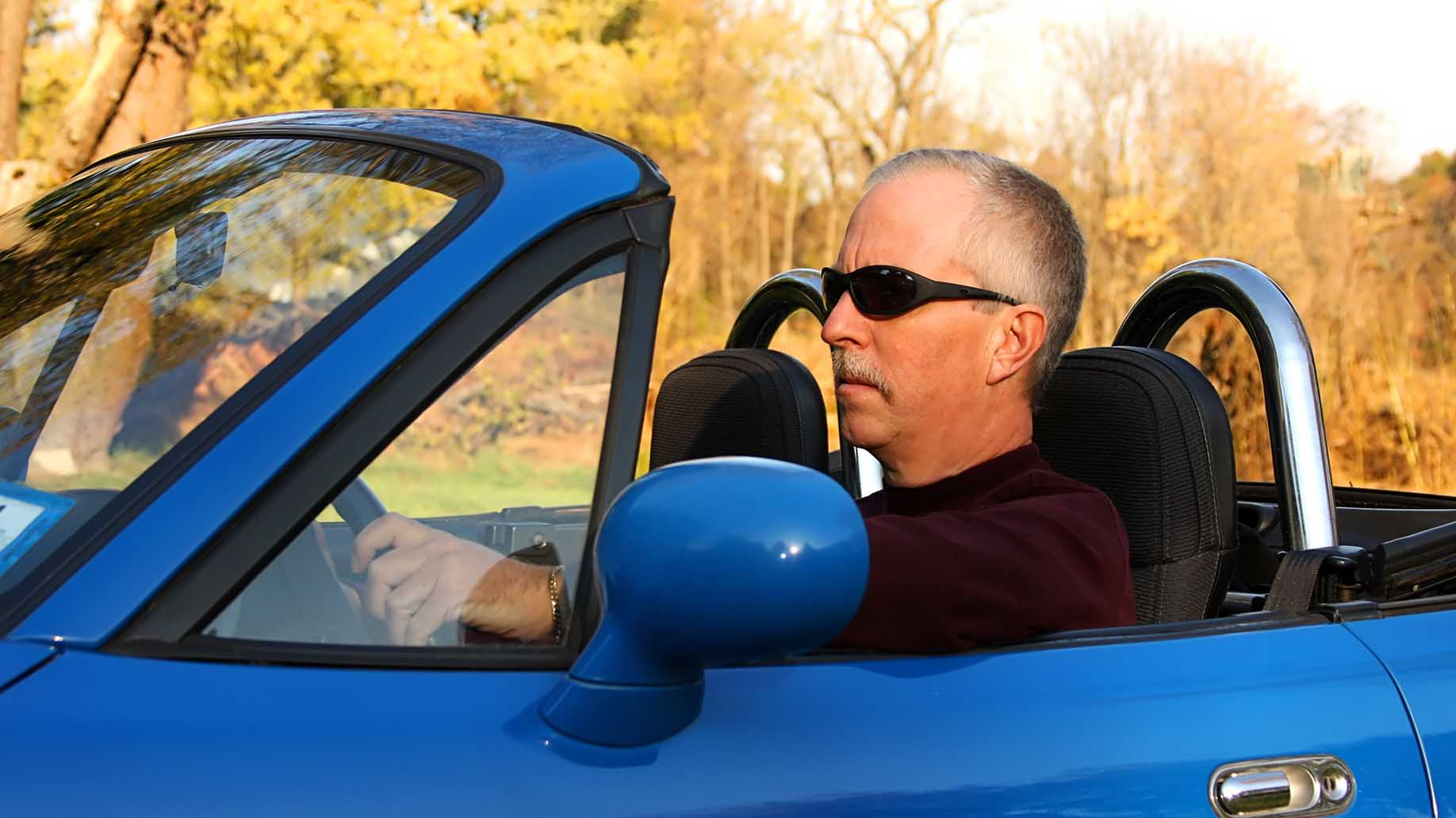 man in a blue convertible trying to fend off a mid-life crisis