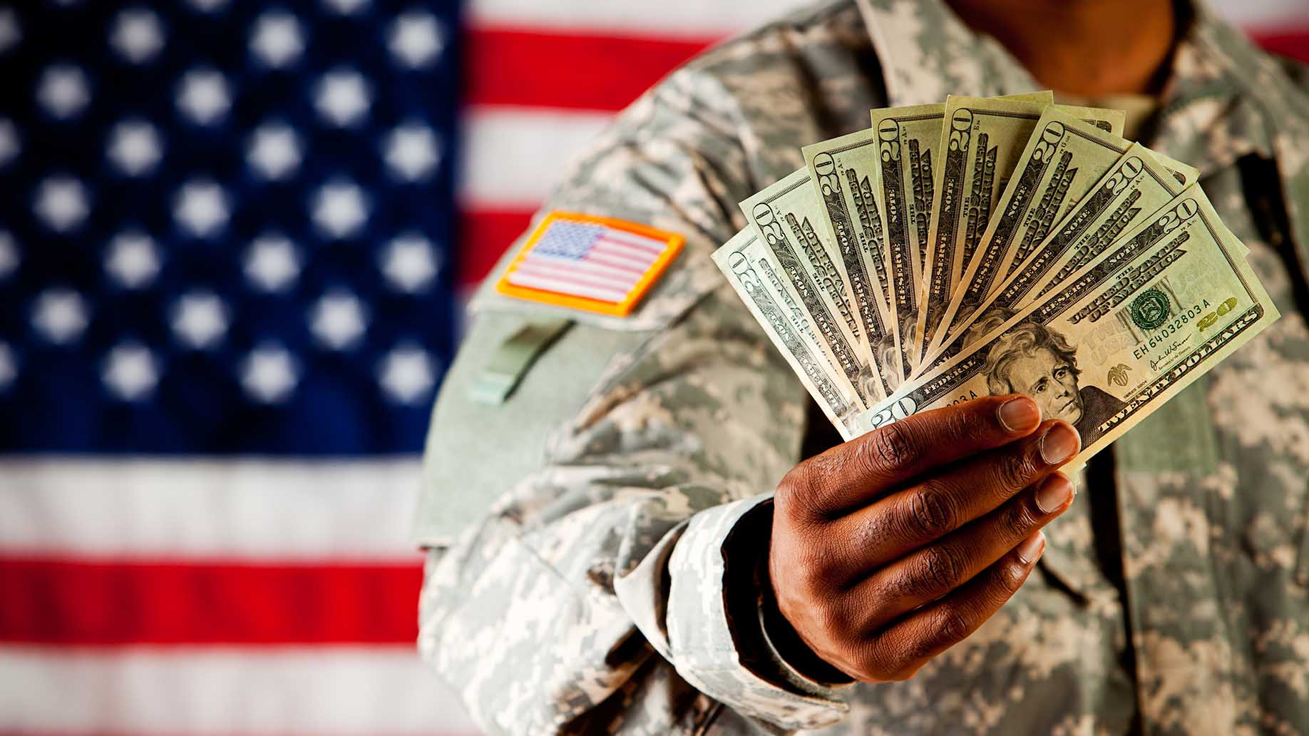 soldier holding out money fan