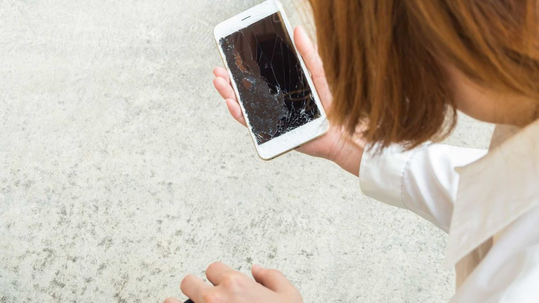 woman picking broken smart phone on the floor