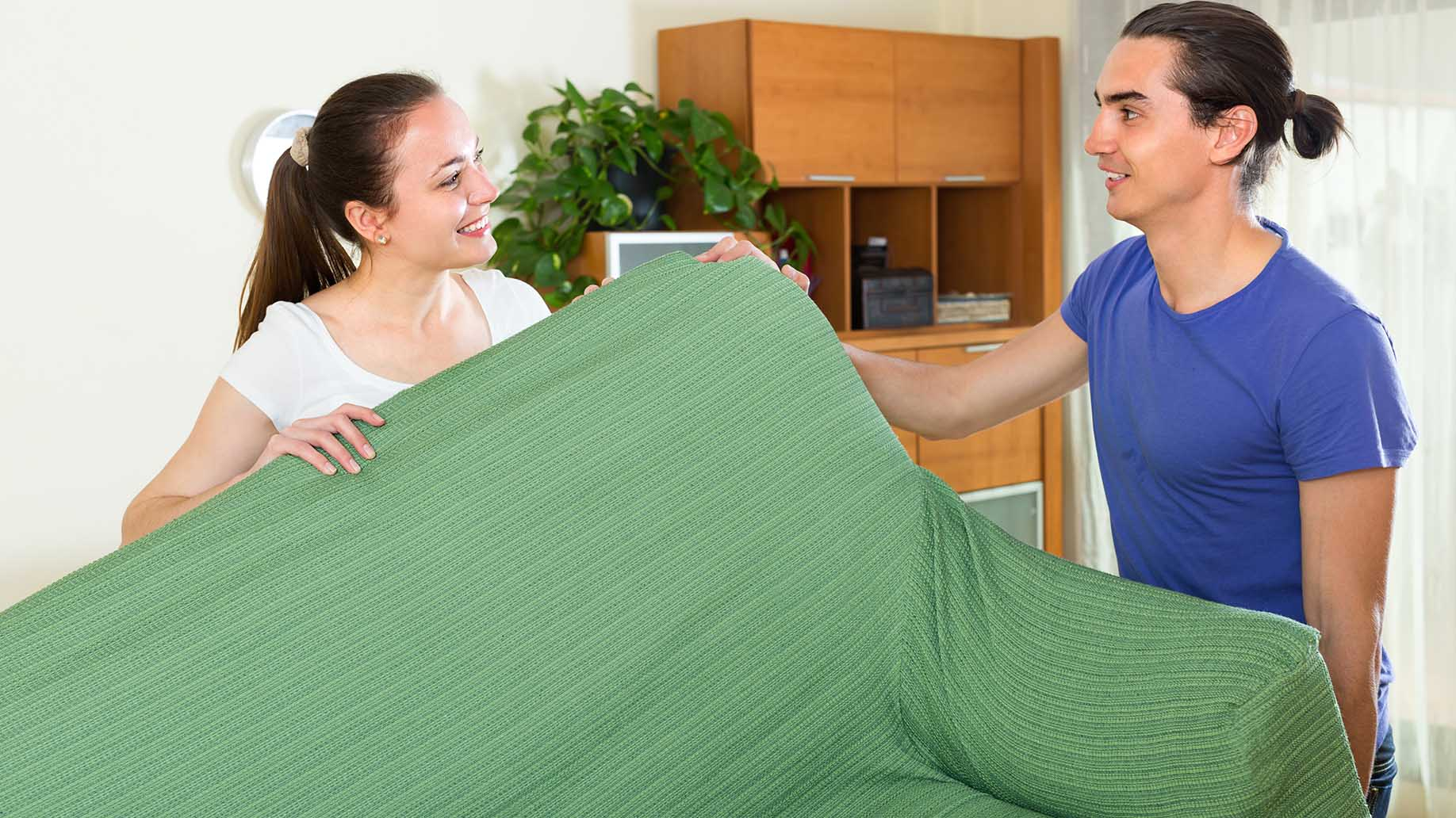positive smiling young couple moving furniture
