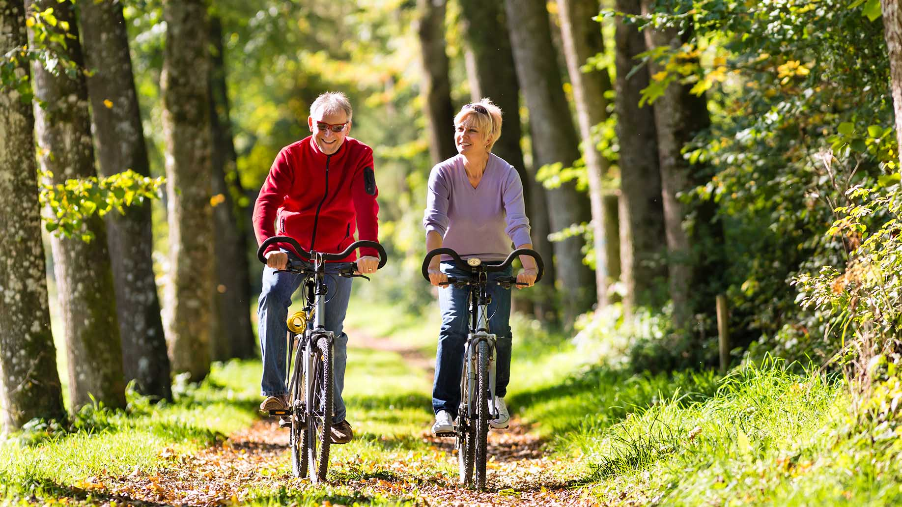 senior man woman exercising bicycles outdoors