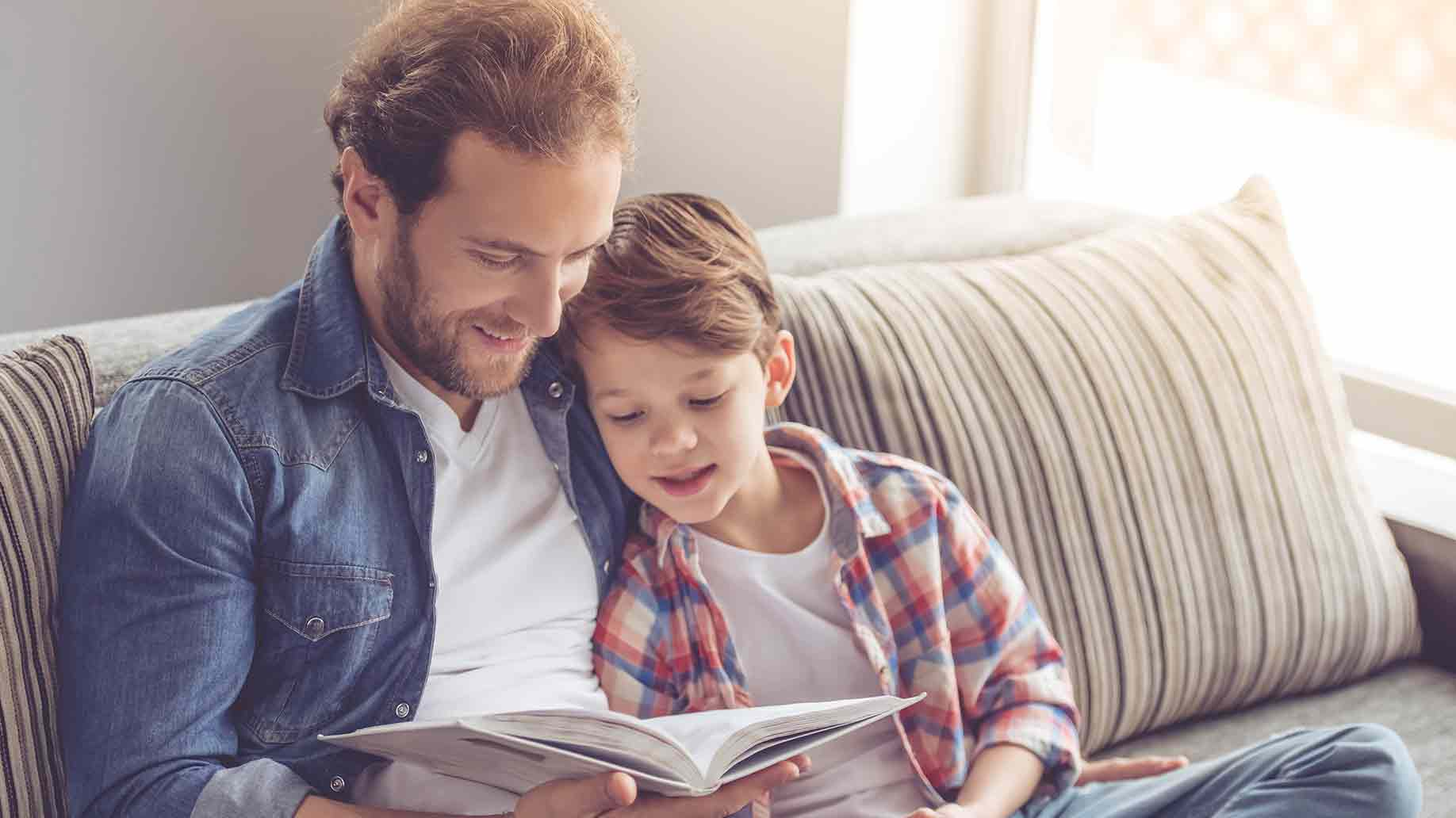 father son reading book smiling while