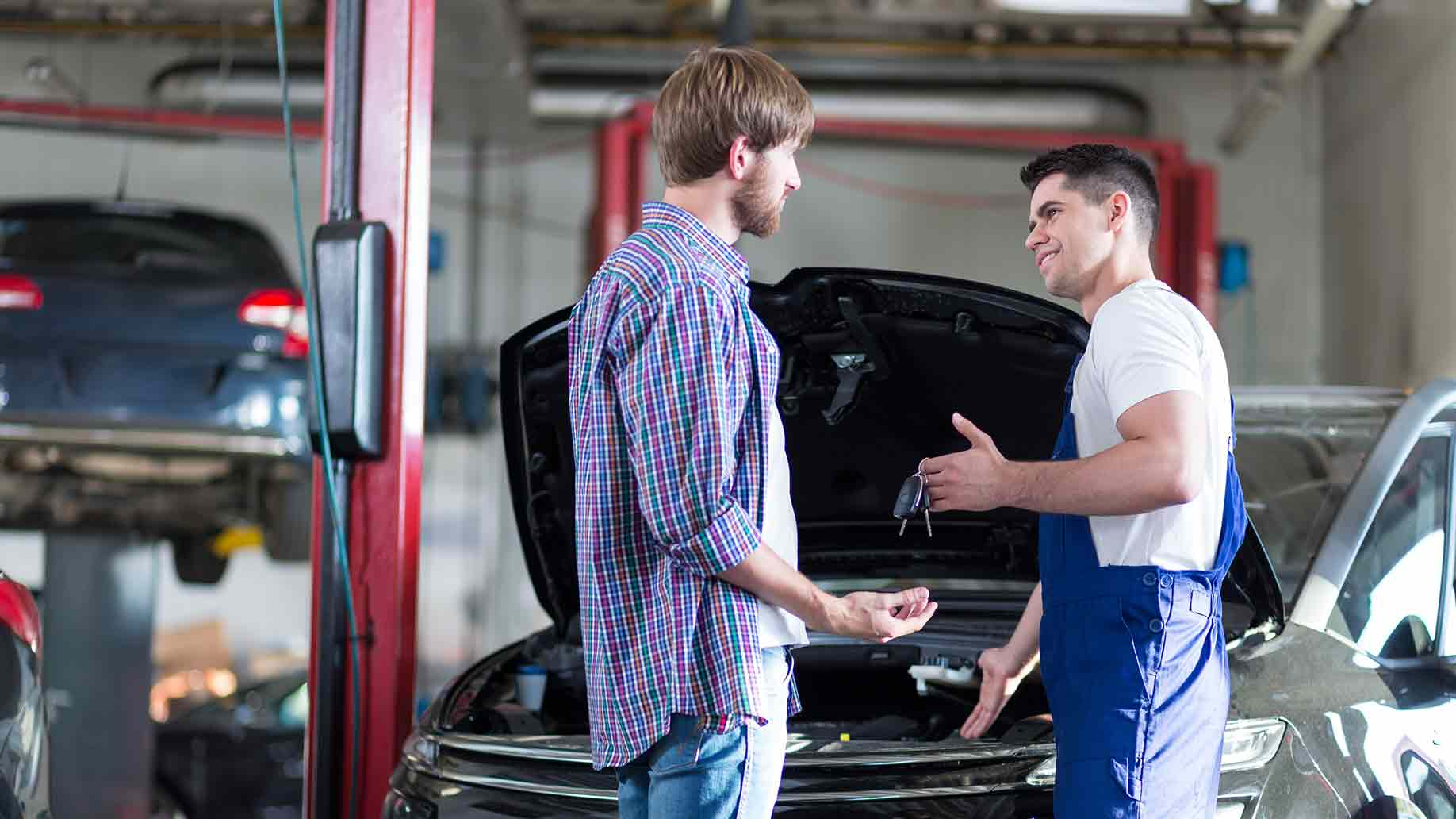 mechanic giving client keys his repaired