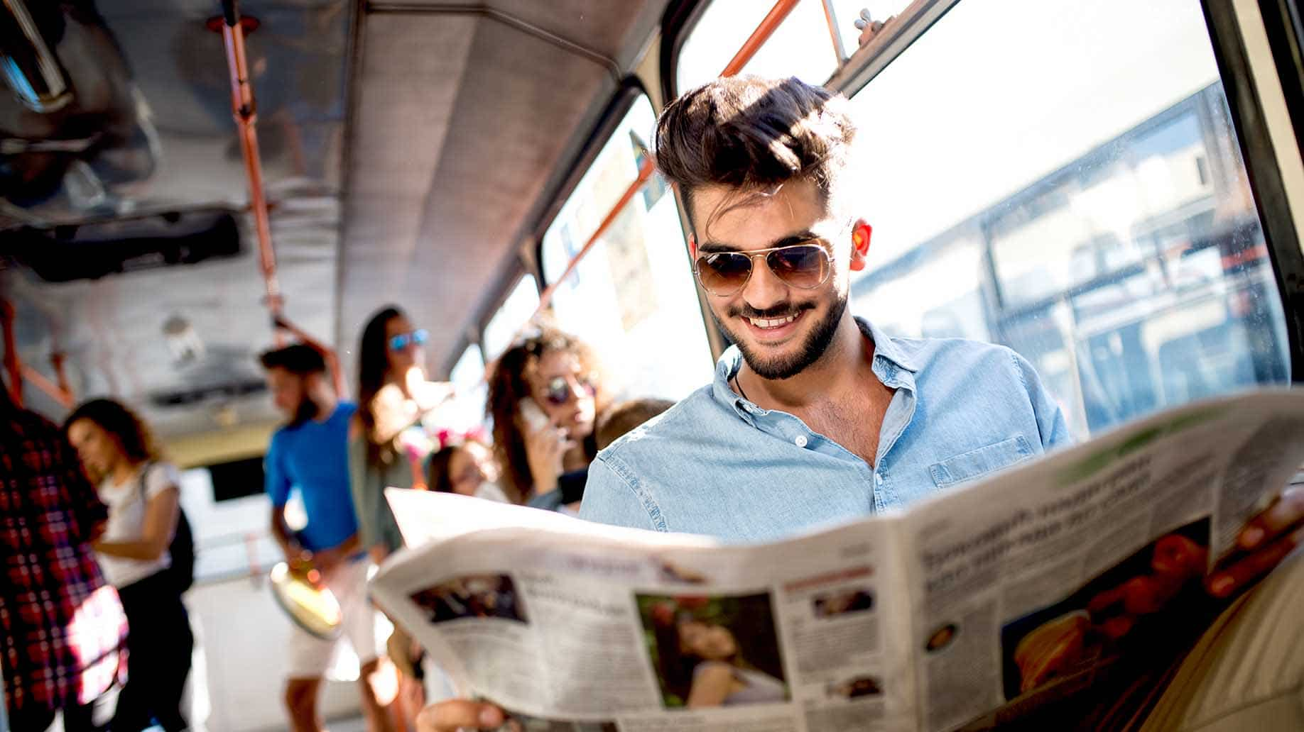 busy businessman sits bus reads newspapers