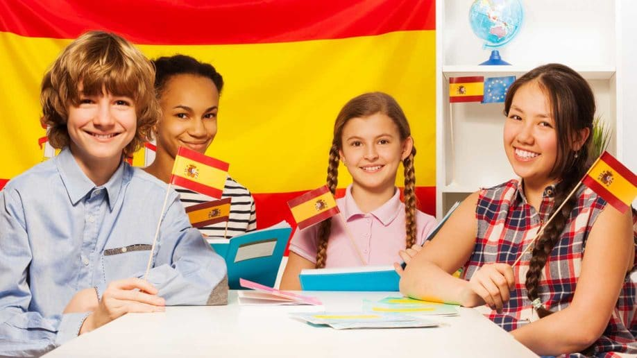 four happy multiethnic students holding flags?