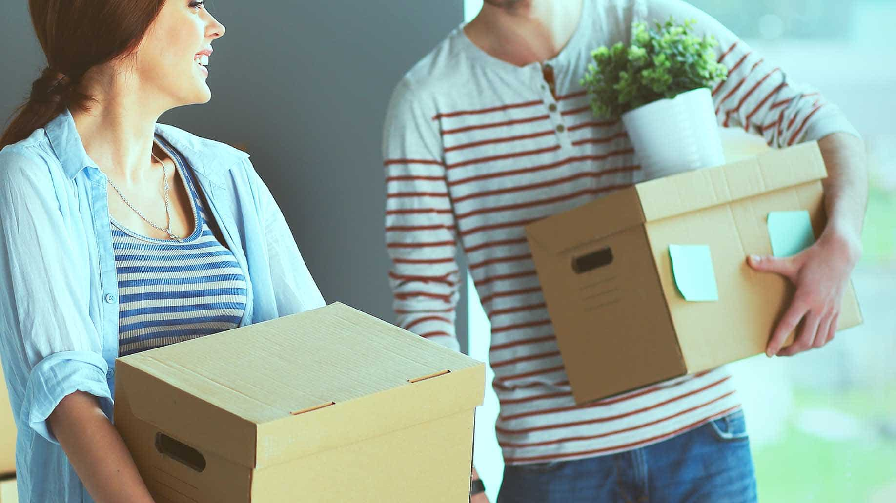 happy young couple unpacking packing boxes