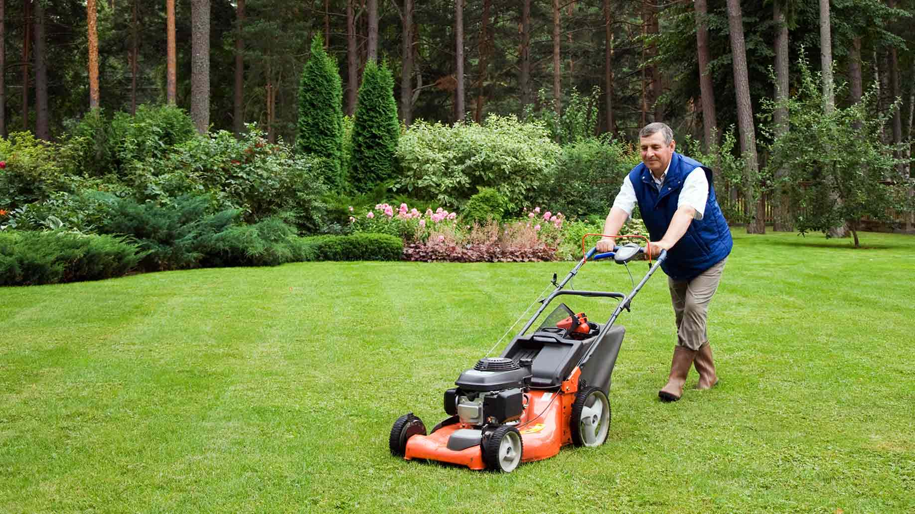 senior man mowing lawn