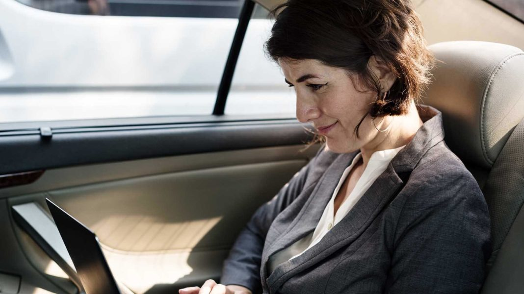businesswoman working using laptop car inside?