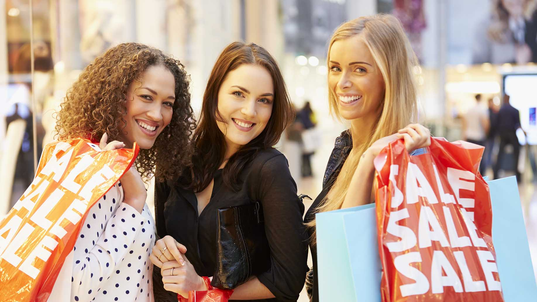 three female friends shopping mal together