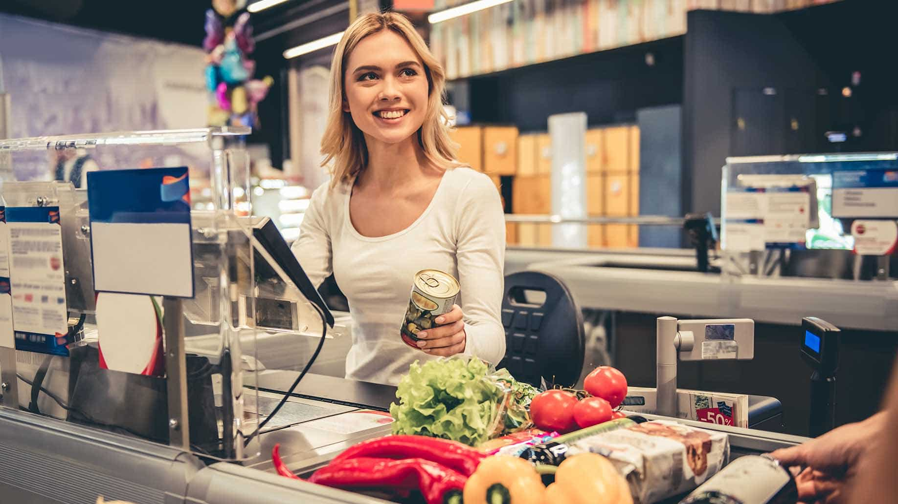 beautiful young cashier smiling while working