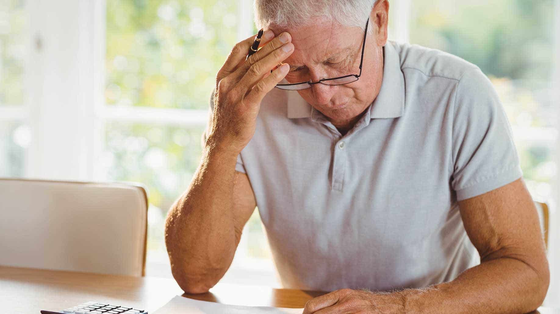 worried senior man tax documents home
