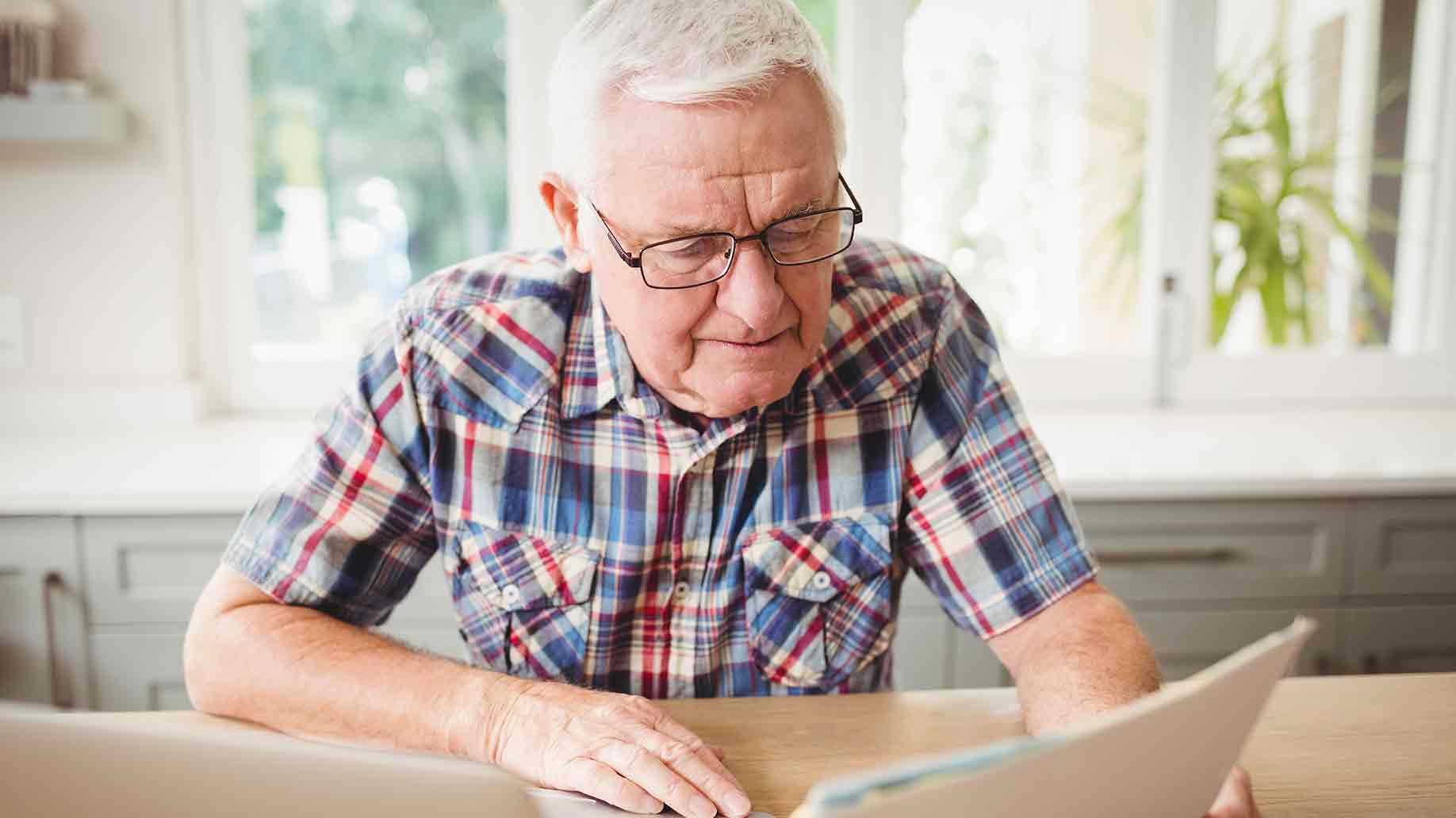 worried senior man looking document while