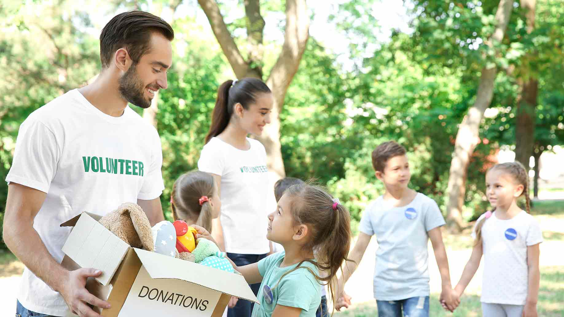 young volunteers children box donations outdoors