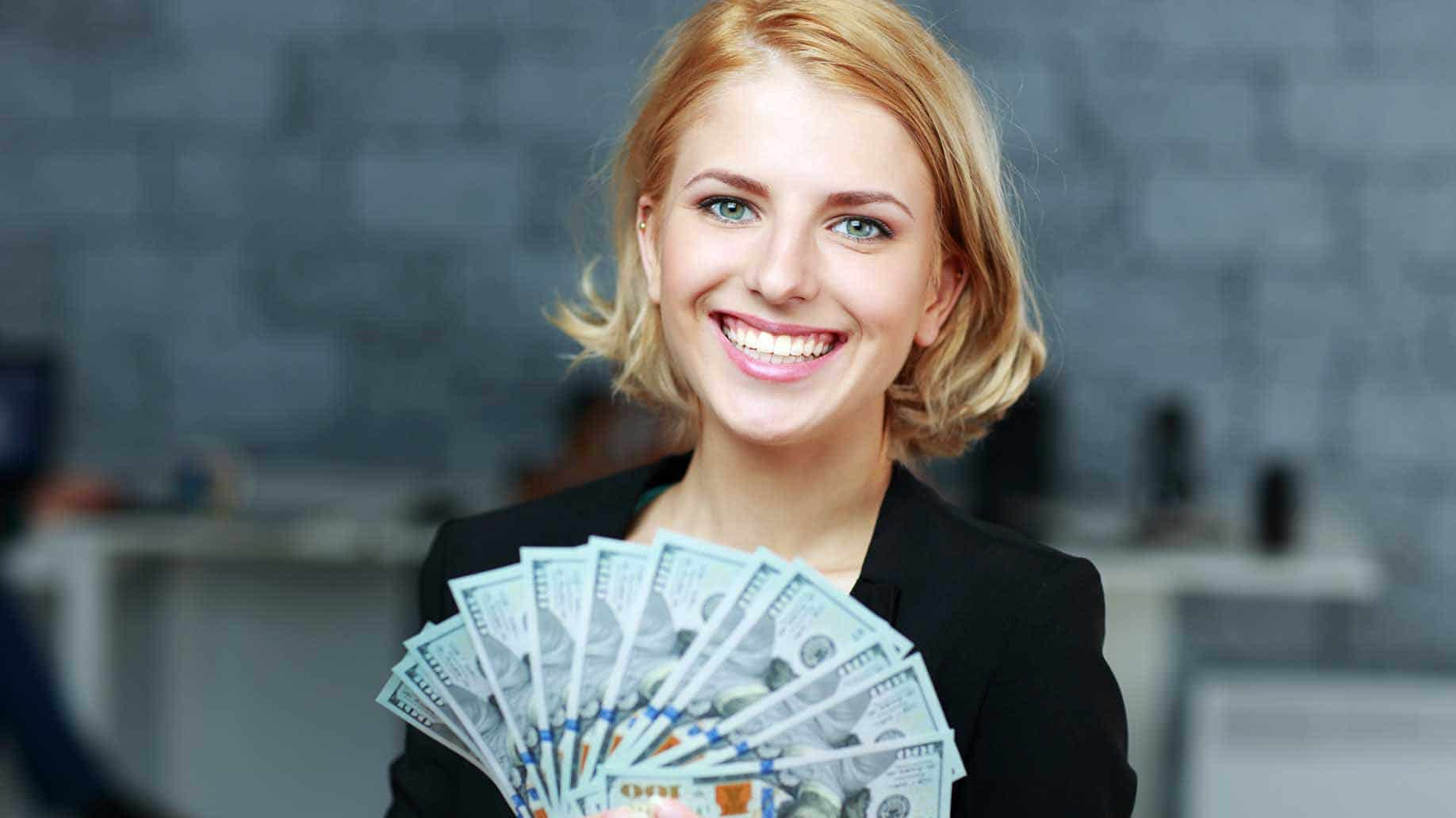 happy smiling businesswoman holding bills dollars