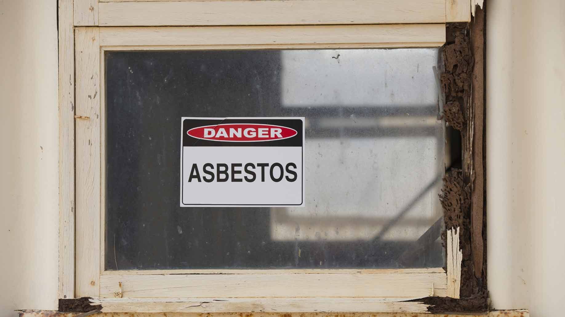 old house with asbestos warning in window