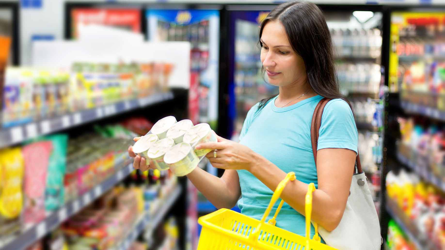 woman buying tinned meat from grocery store
