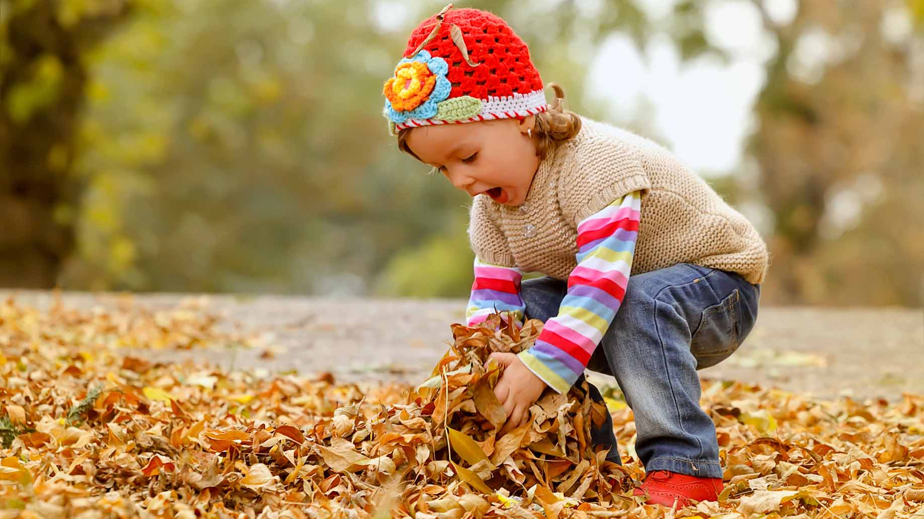 toddler playing with leaves
